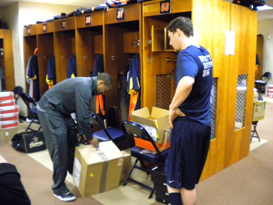 Wes Wright unloads a box while talking to Lucas Harrell.