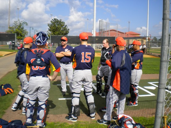 The catchers listen to catching instructor Jeff Murphy.