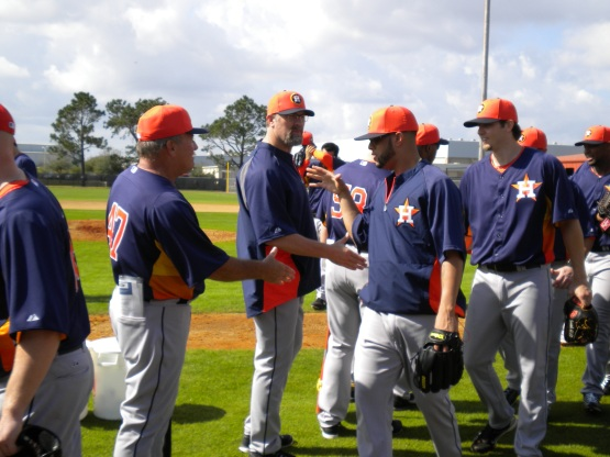 Astros players and coaches shake hands after workout.