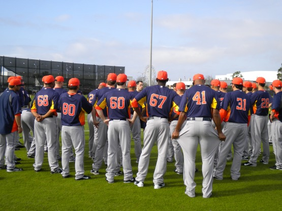 Pitchers and catchers listen to instruction prior to first workout.