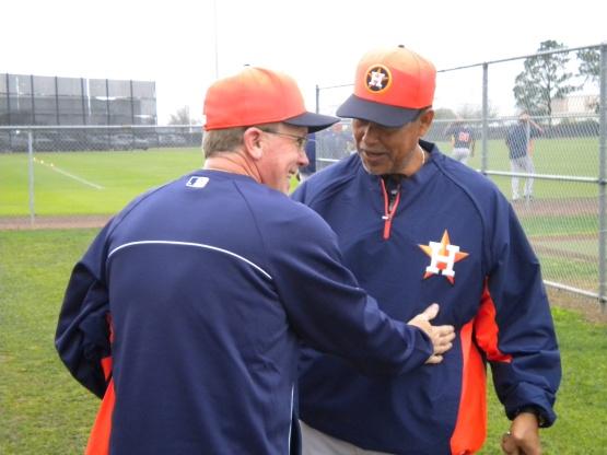 A coach greets bullpen coach Dennis Martinez.